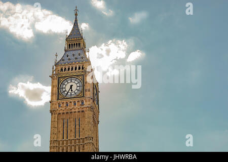 Elizabeth Tower with the clock and the bells of Big Ben in front of a bright blue sky with luminous clouds. - Stock Photo