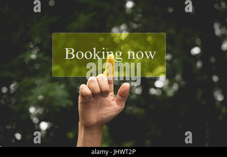 Hand of person presses button booking now. Hand pressing on virtual screen and selecting booking now. - Stock Photo