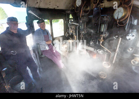 The driver and fireman on the steamy footplate of  Ex-BR loco 78018 waiting to take their train to Minehead on the - Stock Photo