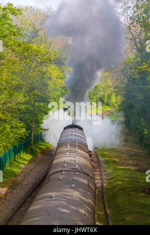 Ex-BR loco 78018 makes a steamy and smoky departure from Bishops Lydeard station with a train to Minehead on the - Stock Photo