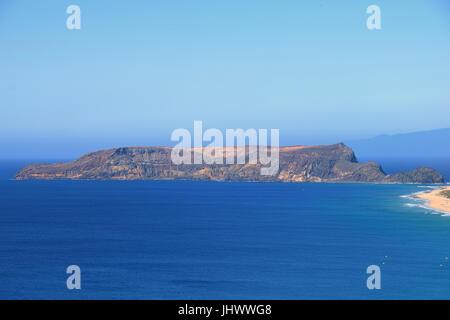 Ilheu da Cal barren uninhabitated island to the south of Ponta Da Calheta, Porto Santo with Madeira to the right - Stock Photo
