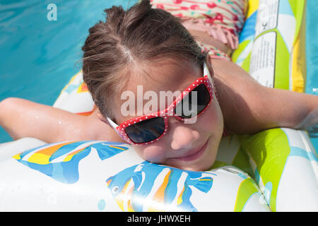 Smiling young girl on an inflatable lie low in a swimming pool - Stock Photo