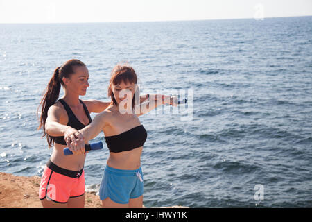 fitness trainer shows woman sport exercises