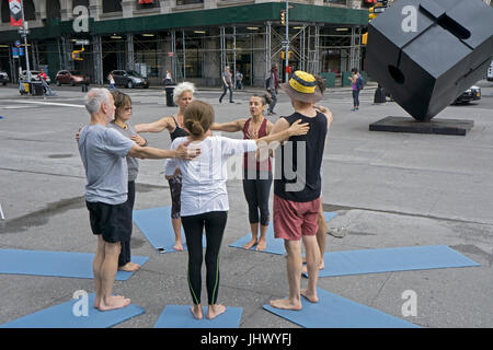 At the conclusion of an outdoor free yoga class the instructor (maroon top) leads the group in a moment of thought - Stock Photo