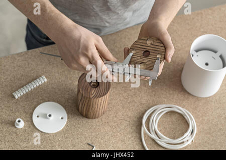Hands of a man with a caliper who is measuring a size of a round wooden billet in the workshop. Under his hands - Stock Photo