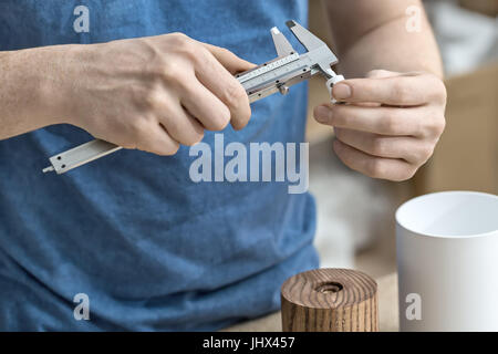 Measuring process in the workshop. Man is using a caliper on the white metal detail. Under his hands there are wooden - Stock Photo