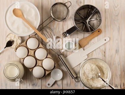 Kitchen utensils and tools for homemade baking on a light wooden background. Selective focus. - Stock Photo