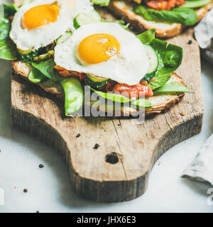 Bread toasts with fried eggs and fresh vegetables, square crop - Stock Photo