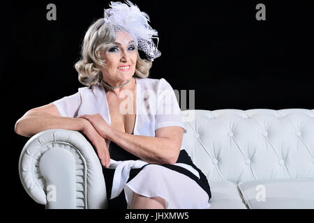 Happy fashionable elderly woman sitting on a white sofa - Stock Photo