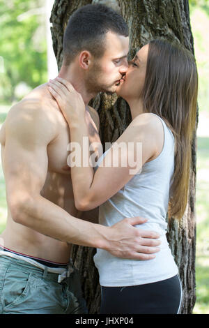 Young couple in love, young man and woman, they are kissing in the park. They are athletes and they take a break - Stock Photo