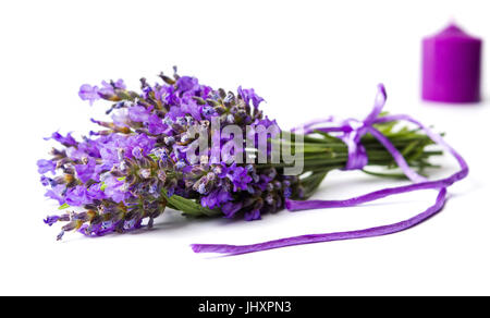 Lavender flowers bouquet and purple candle on white - Stock Photo