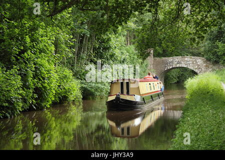 Narrowboat holiday makers navigate the Monmounthshire and Brecon Canal near Llangynidr in the Brecon Beacons, Powys, - Stock Photo