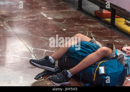 A boy sleeps in a station waiting for his train - Stock Photo