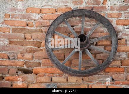 Old cartwheel hangs by a brick wall - Old cartwheel is hanging on a brick flow, Altes Wagenrad hängt an einer Ziegelmauer - Stock Photo