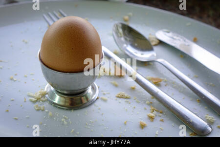 Boiled brown egg in eggcup on a wooden table. Close up. - Stock Photo