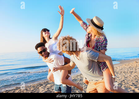 Cheerful young friends enjoying summertime on the beach - Stock Photo
