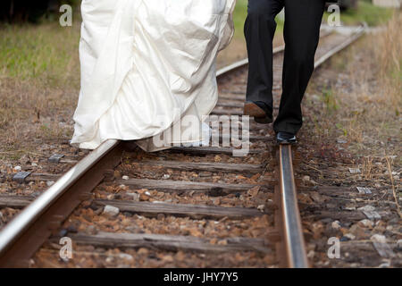 Bride and groom run on rail in the railway station - bridal couple At a railway station, walking on straight, Brautpaar - Stock Photo