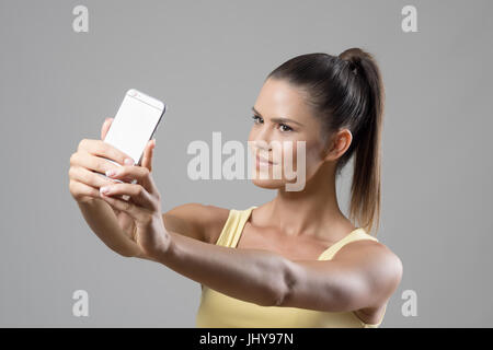 Fit sporty young woman in tank top with ponytail taking selfie photo looking at phone over gray studio background. - Stock Photo