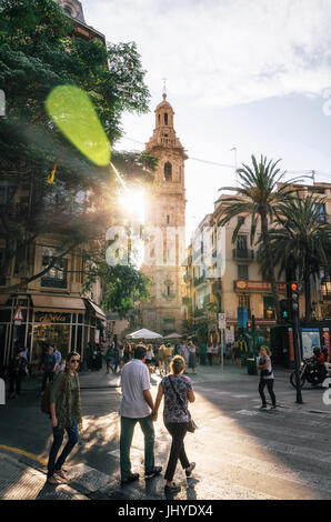 Valencia, Spain - June 3, 2017: Street view with Santa Caterina tower and passing tourists at sunset with bright - Stock Photo