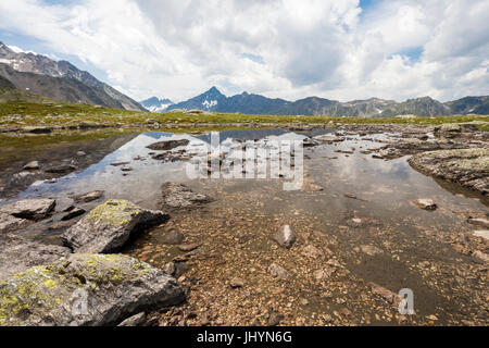 Clouds on rocky peaks reflected in the alpine Lake Schottensee, Fluela Pass, canton of Graubunden, Engadine, Switzerland, - Stock Photo