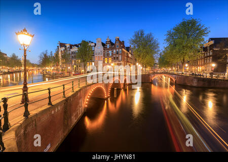 Dusk lights on typical buildings and bridges reflected in a typical canal, Amsterdam, Holland (The Netherlands), - Stock Photo