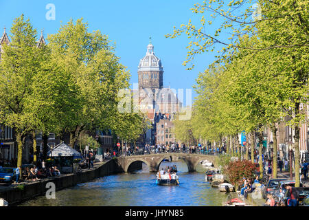 The Old Church (Oude Kerk) framed by boats and bridges in a canal of the river Amstel, Amsterdam, Holland (The Netherlands) - Stock Photo