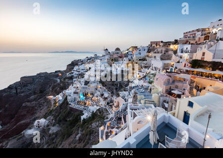 Sunset view over the whitewashed buildings and windmills of Oia, Santorini, Cyclades, Greek Islands, Greece, Europe - Stock Photo