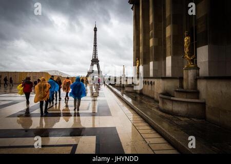 Heading towards the Eiffel Tower, tourists brave the rain in colourful ponchos at the Palais De Chaillot, Paris, - Stock Photo