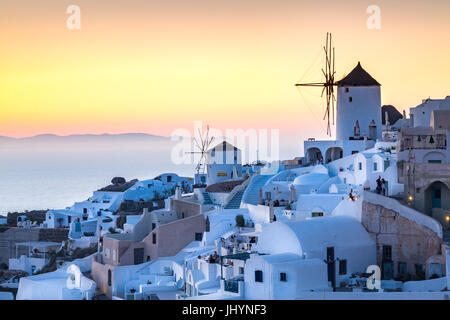 Sunset over the white stone buildings and windmills of Oia on the tip of Santorini's caldera, Santorini, Cyclades, - Stock Photo