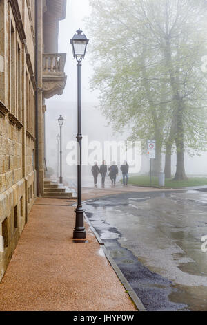 People walking on a street in the mist - Stock Photo