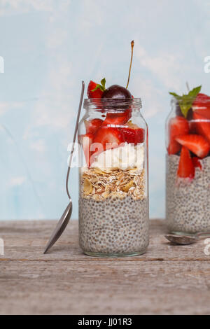 Chia pudding with strawberries, cherries and muesli. Love for a healthy vegan food concept. - Stock Photo