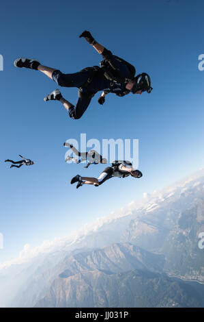 Four skydivers lining up on a tracking jump above Locarno, Switzerland with the Alps in the background - Stock Photo