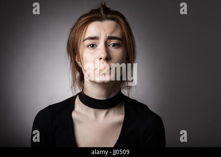 sad girl with plaster on her mouth looking at camera at gray background - Stock Photo