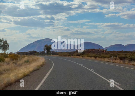 Kata Tjuta in the semi shaded afternoon sun,view from the main road, cloudy blue sky, red, dry, desert landscape, - Stock Photo