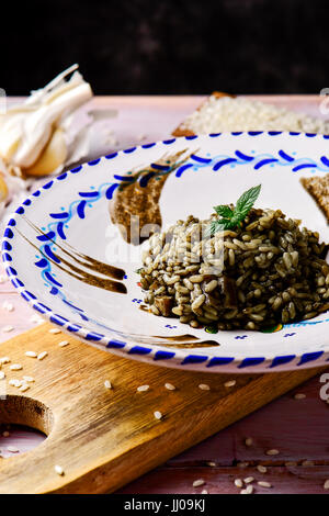 closeup of a white and blue ceramic plate with spanish arroz negro or black paella, a variation of the seafood paella - Stock Photo