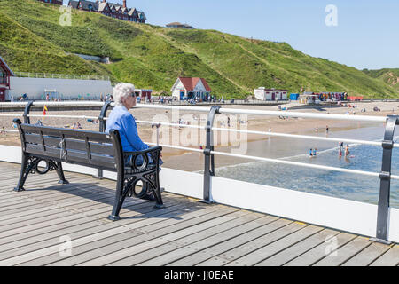 A mature woman sat on a bench by herself looking out to sea at Saltburn by the Sea,England,UK - Stock Photo
