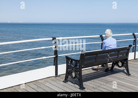 A mature woman sat on a bench by herself looking out to sea from the pier at Saltburn by the Sea,England,UK - Stock Photo