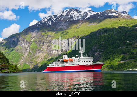Small cruise ship G Adventures Expedition anchored in scenic Geirangerfjorden or Geiranger Fjord in summer. Geiranger - Stock Photo