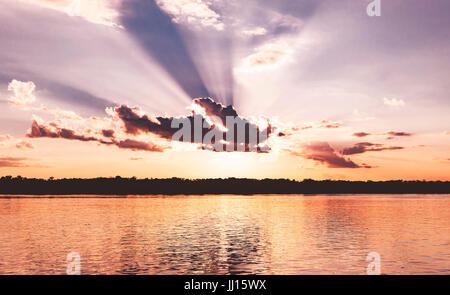 Amazing sunset at Rio Madeira in Porto Velho RO Brazil. Sunset at golden hour with some sunbeams, shadows from clouds - Stock Photo