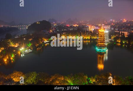 Evening view of the Gold and Silver Pagodas, also known as the Sun and Moon Pagodas, reflected in Shan Lake  Guilin, - Stock Photo