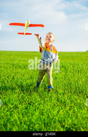Happy boy playing with toy airplane against blue summer sky and green field background. - Stock Photo