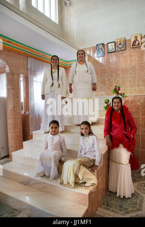 Women and girls of a wealthy Roma gypsy family posing on the staircase of their luxury house, Ivanesti, Romania - Stock Photo