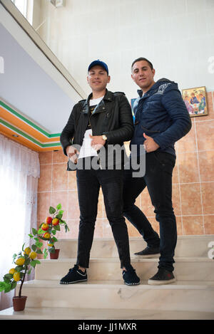 Two boys of a wealthy Roma gypsy family posing on the staircase of their luxury housey, Ivanesti, Romania - Stock Photo