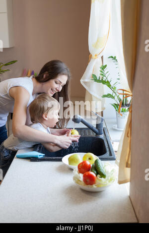 the little boy is helping mom in the kitchen - Stock Photo