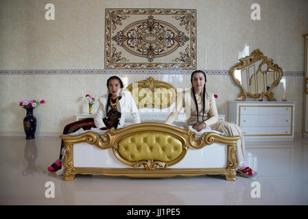 Girls of a wealthy Roma gypsy family posing in the luxurious bedroom of their house, Ivanesti, Romania - Stock Photo