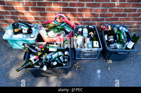 Glass bottles placed in recycling box outside property for collection by council refuse collectors in the village - Stock Photo