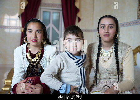 Kids of a wealthy Roma gypsy family posing in the luxurious bedroom of their house, Ivanesti, Romania - Stock Photo