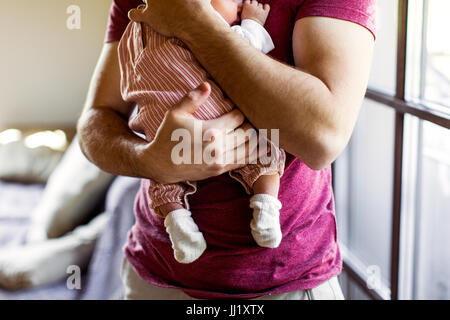 Unrecognizable young father at home holding his newborn baby gir - Stock Photo