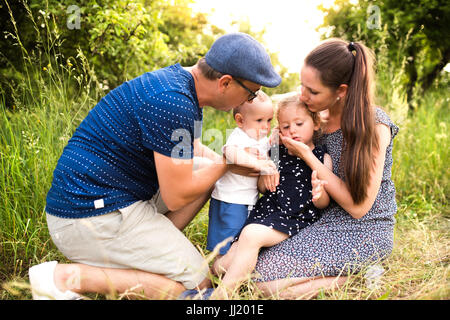 Young family with little children in sunny summer nature - Stock Photo