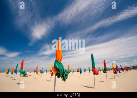 Colourful beach umbrellas (parasols) on Deauville sandy beach (plage). - Stock Photo